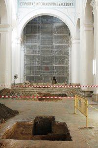 La imagen muestra el retablo mayor protegido por andamios y mallas de seguridad, y una de las criptas de piedra encontradas en la prospección arqueológica. Contenía desechos del fuego de 1737.