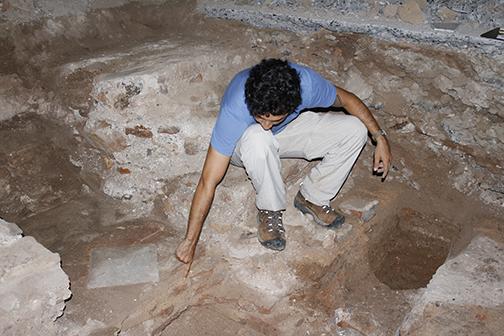 El arqueólogo Jonathan Hernández enseña la baldosa de mármol que decora el presbiterio original del siglo 18.