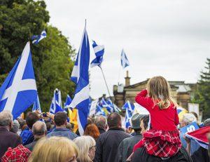Partidarios de la independencia de Escocia del Reino Unido portan la bandera nacional por las calles de Edimburgo durante una manifestación celebrada antes del referéndum de septiembre de 2014.